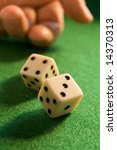 hand rolling dice onto a green baize - stock photo