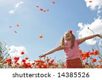 Little girl meadow throwing poppy petals, blue sky in background - stock photo