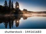 The sun shines through pine trees and fog at sunrise, at Spruce Knob Lake, Monongahela National Forest, West Virginia.