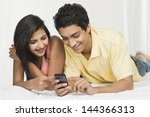 couple looking at a mobile... | Shutterstock . vector #144366313