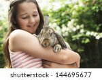 Stock photo happy young girl holding bunny rabbit in the backyard 144695677