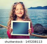 Child On The Beach With Tablet...