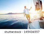 sunrise sailing man on boat in... | Shutterstock . vector #145436557