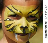 close-up of child painted in the face as a tiger - stock photo