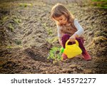 Little Girl Watering Plants In...