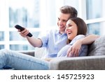 couple on sofa with tv remote  | Shutterstock . vector #145725923