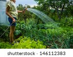 Young Woman Watering Her Garden