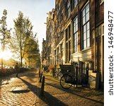 Stock photo a stranger in the streets of the city amsterdam accompanied by long shadows strolled between the 146948477