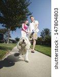 Stock photo low angle view of a couple walking dog along pavement 147804803
