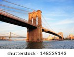Stock photo brooklyn bridge over east river viewed from new york city lower manhattan waterfront at sunset 148239143
