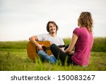 Young Man Playing Guitar To Hi...