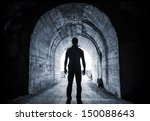 Young Man Stands In Dark Tunne...