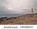 Lighthouse With A Lightbeam At...