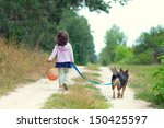 Stock photo little girl with dog walking on the sand road 150425597