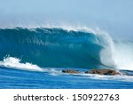 Small photo of A beautiful blue wave crashes into the rocks at Inhaca Island, Mozambique.