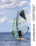 Small photo of Back view of two windsurfers in action mooving parallel to eath other