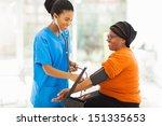 smiling african nurse checking... | Shutterstock . vector #151335653