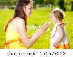 mother feeds baby girl outdoors ... | Shutterstock . vector #151579523
