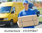 Small photo of Smiling young male postal delivery courier man in front of cargo van delivering package