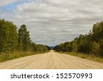 A Gravel Road Between Trees In...