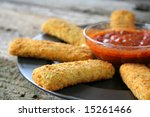 Appetizer of mozzarella cheese sticks with marinara sauce. Used a shallow depth of field. - stock photo