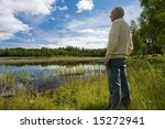 Senior man enjoying a walk by a lakeside - stock photo