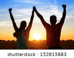 Stock photo successful couple of young athletes raising arms to golden summer sunset sky after training 152815883