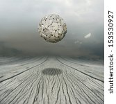 Small photo of Artistic metaphysical background representing a ball sculpture floating in the air above a wooden floor with the sky on the background
