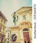Small photo of Vintage looking Statue of writer Alessandro Manzoni in front of San Fedele church, Milan, Italy