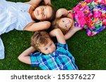 happy children lying on a meadow | Shutterstock . vector #155376227