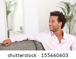 young man sitting on the couch   Shutterstock . vector #155660603