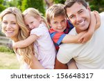 Small photo of Portrait Of Happy Family In Garden