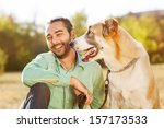Stock photo man and central asian shepherd walk in the park he keeps the dog on the leash 157173533