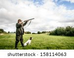 Small photo of Hunter with dog aiming with his rifle