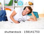 young man relaxing on carpet... | Shutterstock . vector #158141753