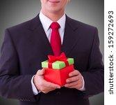 Businessman Holding Gift Box...