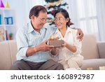smiling woman giving a xmas... | Shutterstock . vector #160892987