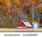 An Old Red Barn Stands Between...