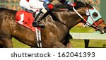 Stock photo two horses and jockeys come aross finish line neck and neck number one 162041393