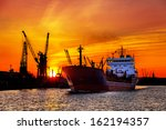 Ship And Cranes At Sunset In...