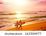 couple of surfers walks along... | Shutterstock . vector #162504977