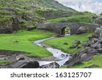 an old stone bridge carries a... | Shutterstock . vector #163125707