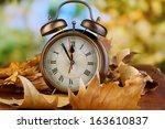 Old Clock On Autumn Leaves On...