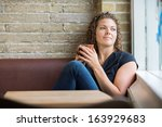 thoughtful woman holding coffee ... | Shutterstock . vector #163929683