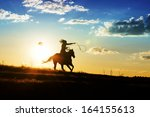 Stock photo girl loses hat while riding horse at sunset 164155613
