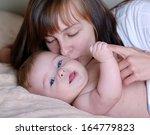 portrait of mother kissing her... | Shutterstock . vector #164779823