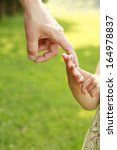 a parent holds the hand of a... | Shutterstock . vector #164978837