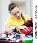 Small photo of inconsiderate woman searching something in handbag at home
