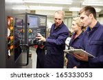 Small photo of Engineer Teaching Apprentices To Use Computerized Lathe
