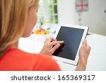 woman using digital tablet at... | Shutterstock . vector #165369317